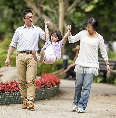 Image of mom and dad swinging daughter while walking outside